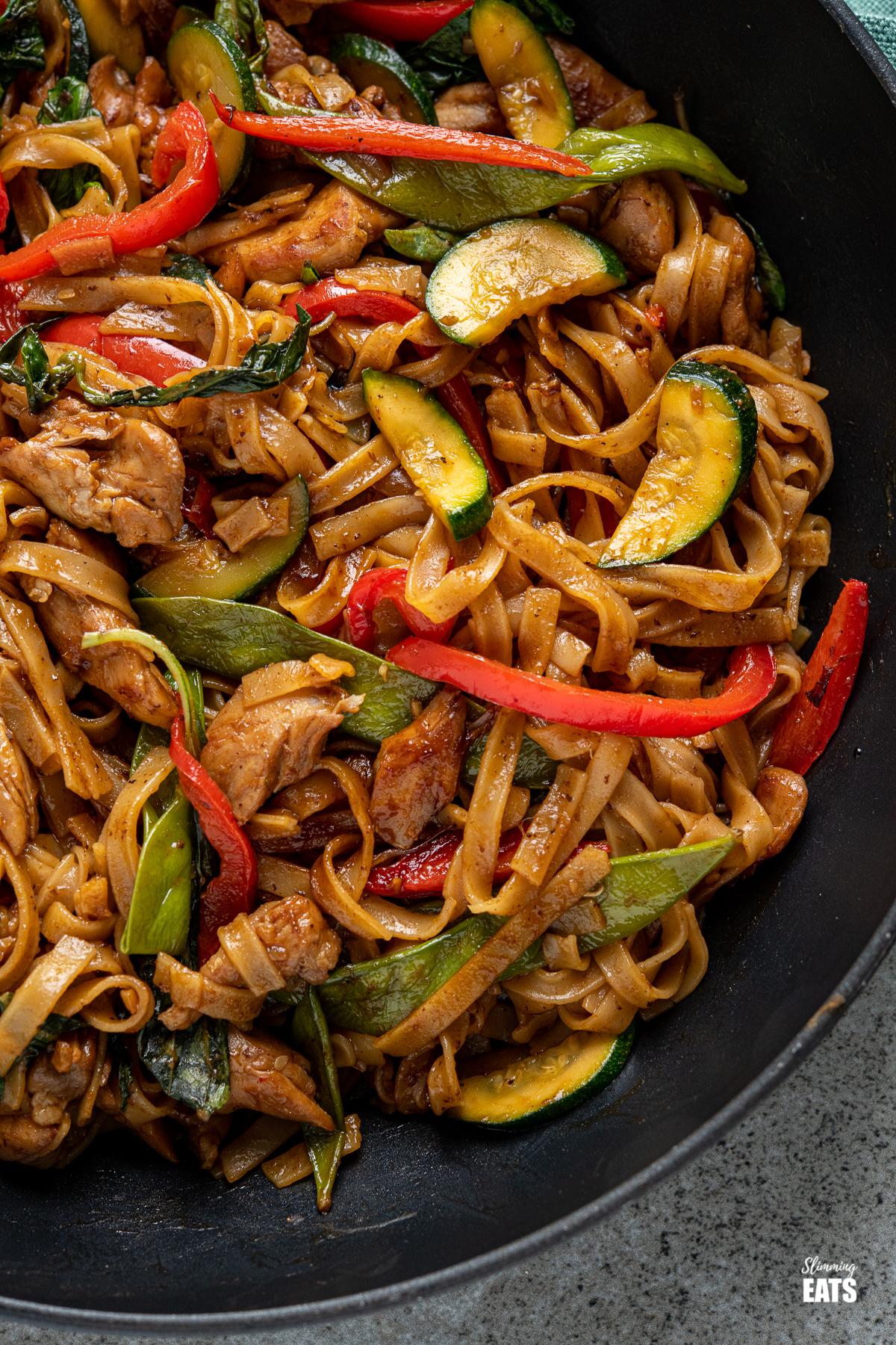 酒醉的面条-鸡肉,蔬菜和米粉在一个黑色的平底锅辛辣可口的酱汁