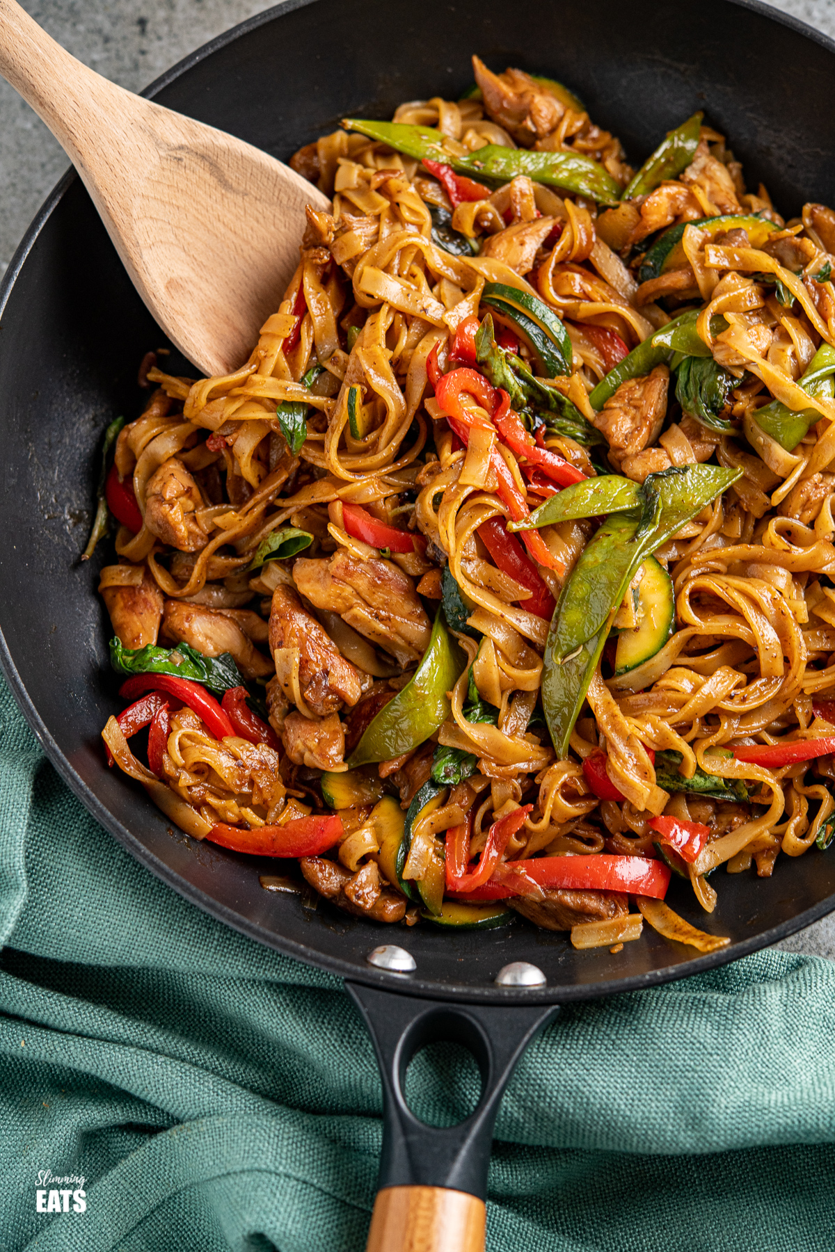 醉酒的面条 - 鸡肉,蔬菜和米粉在一只辣的香味酱中的黑色锅里用木手柄